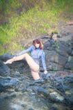 Turnermädchen, das auf einem Stein sitzt Lizenzfreie Stockfotografie