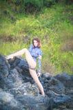 Turnermädchen, das auf einem Stein sitzt Stockbild