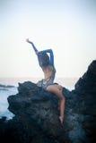 Turnermädchen, das auf einem Stein sitzt Stockfotografie