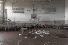 Turnhalle mit Staplungsschreibtischen in verlassener Highschool stockfoto