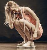Turnhallenfrau auf Gewichtsskala Stockbild