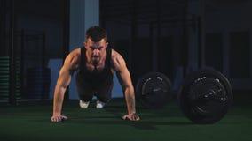 Turnhallenmannliegestützstärke-Liegestützübung mit Dummkopf in einem crossfit Training stock video footage