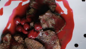 Turning around dish of meat and red sauce on the plate stock video