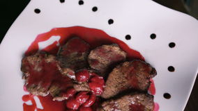 Turning around dish of meat and red sauce on the plate in 4K stock video footage