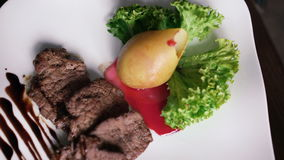 Turning around dish of meat and vegetables on the plate in 4K.  stock video footage