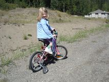 Turning the bike. Little girl learning to ride around the neighborhood royalty free stock photo