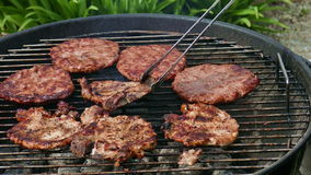 Turning Burgers And Steaks On Grill stock video footage