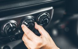 Turning on car air conditioning system. Finger hitting car emergency light botton,Hand tuning fm radio button in car panel Stock Photography