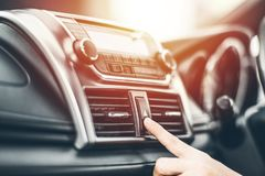 Turning on car air conditioning system. Finger hitting car emergency light botton,Hand tuning fm radio button in car panel Royalty Free Stock Photos