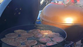 Turning the cutlets on the grill. In the foreground, the hands are opened with a grill cover, in the background in the defocus of the grill stock video footage