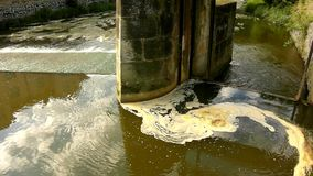 Turning of dirty water above weir on small river with muddy water. Stony wall stock footage
