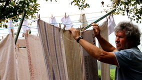 Turning a drying mill with hanging laundry. Towels are drying hanging on a clotheslines mill and a man is turning the mill around stock footage