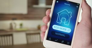 Turning on ECO mode in the Smart House using smartphone application. Man turns on ECO mode in his Smart House using smart home application on his smartphone stock footage