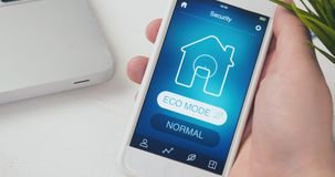 Turning on ECO mode in the Smart House using smartphone application. Man turns on ECO mode in his Smart House using smart home application on his smartphone stock video footage