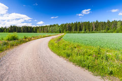 Turning empty rural road under blue sky Royalty Free Stock Images