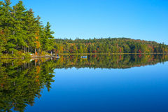 Turning fall on calm water of a lake. The reflection of a forest of fall foliage on Sanborn Pond in Morrill Maine with blue sky Royalty Free Stock Photo