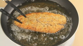 Turning Fried Fish Fillet. Turning a cooked fried fillet of crumbed fish with tongs in a pan of hot oil stock footage