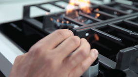Turning on gas cooker and setting fire intensity. Close up shots of kitchen activities while turning on and off fire on gas cooker cooktop stock footage