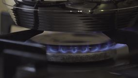 Turning on gas stove with steel pan. Turning on gas stove on black stock footage