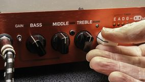 Turning a guitar amplifier volume up. Hand adjusting volume control on a red electric guitar amplifier panel with bass, middle and treble controls visible stock images