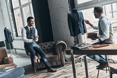 Turning ideas into clothing. Two young fashionable men having a discussion and smiling while standing in workshop royalty free stock photos