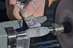 Turning Lath with Purple Boxelder. Skilled hands are turning a segment of purple boxelder on the wood lathe Royalty Free Stock Photography