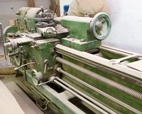 Turning lathe. Huge turning lathe in a carpenter's workshop, covered with wooden dust Royalty Free Stock Photography