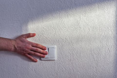 Turning light switch. A hand of a person turning a light switch on a white stone wall royalty free stock photography