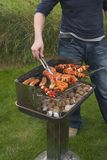 Turning meat on barbecue Stock Image