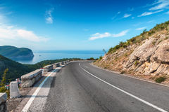 Turning mountain highway with blue sky. And sea on a background Stock Photography