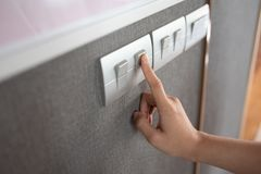 Turning on or off on grey light switch. Asian female right hand is turning on or off on grey light switch over textile texture wall. Copy space stock images