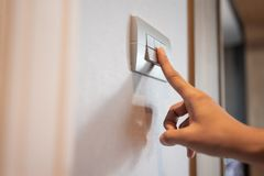 Turning on or off on grey light switch. Close up of Asian female right hand is turning on or off on grey light switch over textile texture wall in Luxury house stock photos