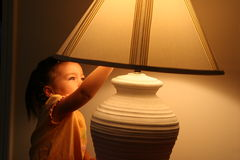 Turning off the lights. A young child is turning off the lamp Stock Images