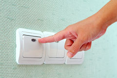 Turning off or turning on the light switch. Turning off or turning on the wall-mounted light switch stock photography