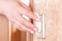 Turning off on wall-mounted light switch - energy saving concept stock image