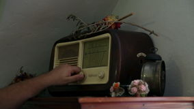 Turning on old retro radio decorated with flowers. Old house with retro radio on closet with flowers stock footage