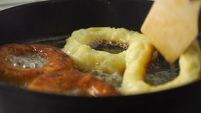 Turning over four frying donuts, close up video. Clip stock footage