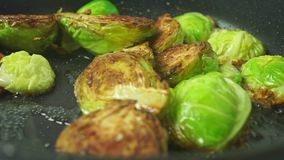 Turning over fried Brussels sprouts close up shot. Clip stock footage