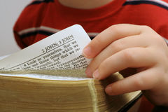 Turning the page of a bible. Shot of a child turning the page of a bible Royalty Free Stock Images