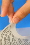 Turning the page of a bible - Proverbs. Upclose of a hand turning the page of a bible on a blue background Stock Images
