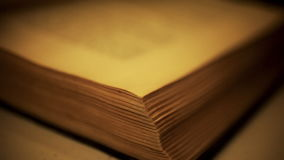 Turning Pages of an Old Book. Close-up macro shot of person turning pages of an old book, all text is out of focus in the background, corner edge of book in stock video