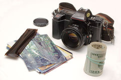 Turning photos into money. An SLR camera sits alongside a pile of photos and strips of 35mm negatives, with a roll of bills standing beside them, on a white royalty free stock photo