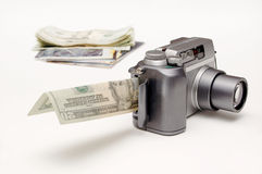Turning photos into money. A digital camera, with the memory card slot open and a bill sticking out of it, sits in front of a small pile of photos and money ( stock image