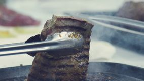 Turning pieces of beef meat - close-up on top of a kitchen tile. A piece of meat overturn a special shovel. Cooking roast beef. The meat in a frying pan. A stock footage