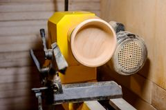 Turning a plate. Turning a wooden plate on a lathe in a carpenter`s workshop Royalty Free Stock Images