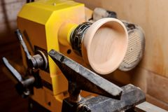 Turning a plate. Turning a wooden plate on a lathe in a carpenter`s workshop Stock Photos