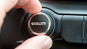 Turning on a Quality button with the word Quality in white lettering stock photography