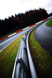 Turning at a race track. A closeup of a bend at a Formula 1 race track. The sides of the track are lined with red and white barriers. Trees are planted further Stock Photos