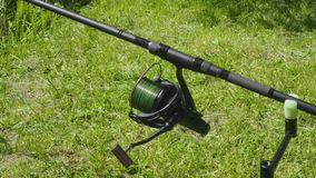 Turning reel on fishing rod. On a background of grass stock video footage