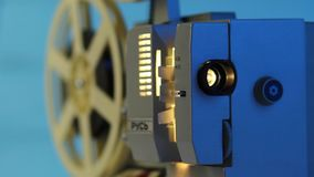 Turning on retro film projector with light beam. Turning on retro film projector, Old style movie camera with dark blue wall, vintage photo effect and light beam stock video